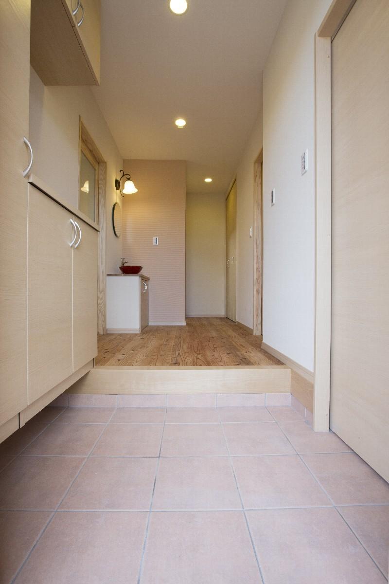 温かみのある色合いの玄関内部。右手にはシューズクロークへのドアがあります