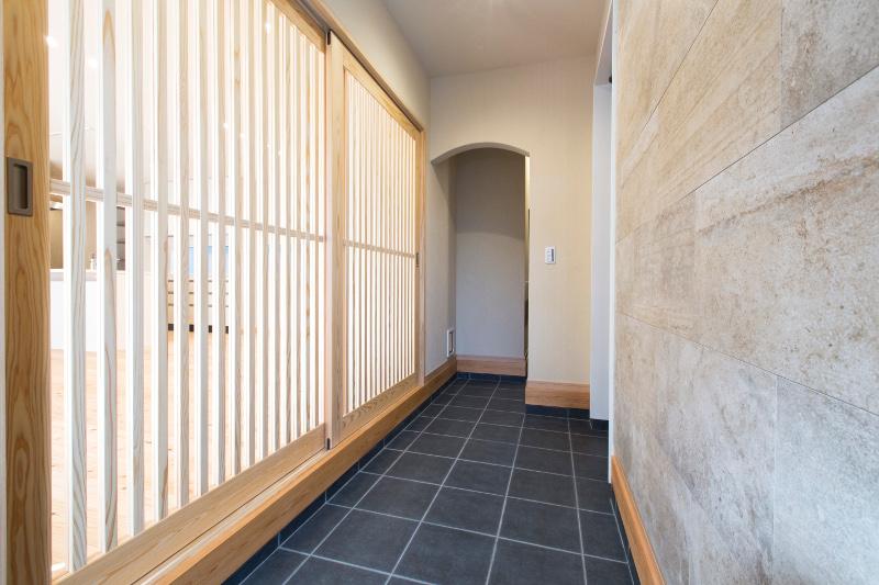 玄関ホール。右手の玄関から入ると、左手にある格子戸が雰囲気を醸し出します。奥はシューズクロースです