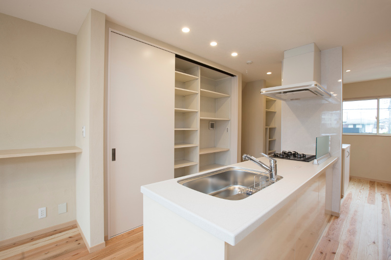 人気のペニュンシュラ型キッチン。背面には大工さんが作った収納棚。炊飯器やレンジも配置できます