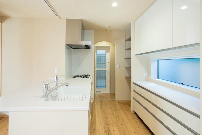 白を基調としたキッチンは収納も十分です。奥には棚やパントリーがあります