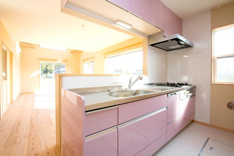 ピンクを基調とした可愛らしい雰囲気のキッチン。パントリーはリビング中ほどに確保