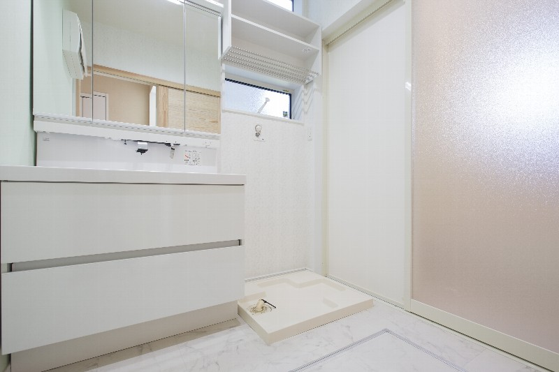 洗面台は十分な収納力があり、大きい扉でバスルームへ